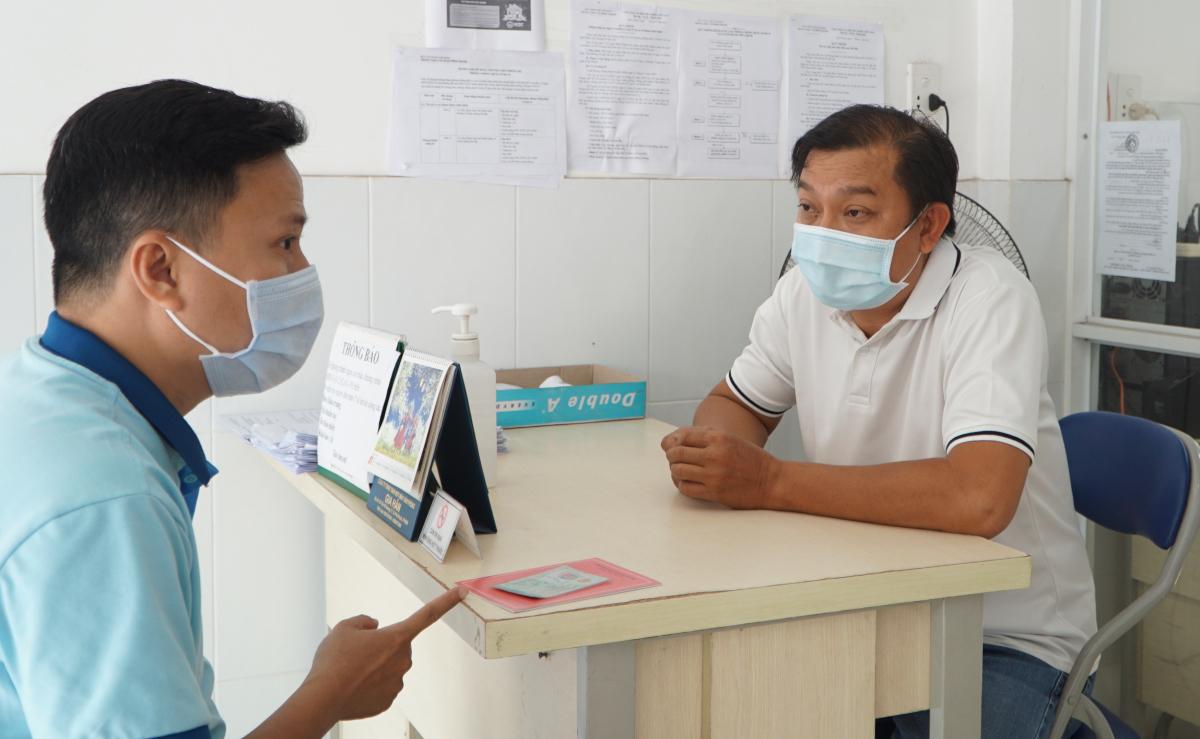 Anh Phú (bên phải) giải đáp thắc mắc khi người dân đến trạm y tế xin giấy chứng nhận không đến từ vùng dịch để về quê. Ảnh: Thư Anh.