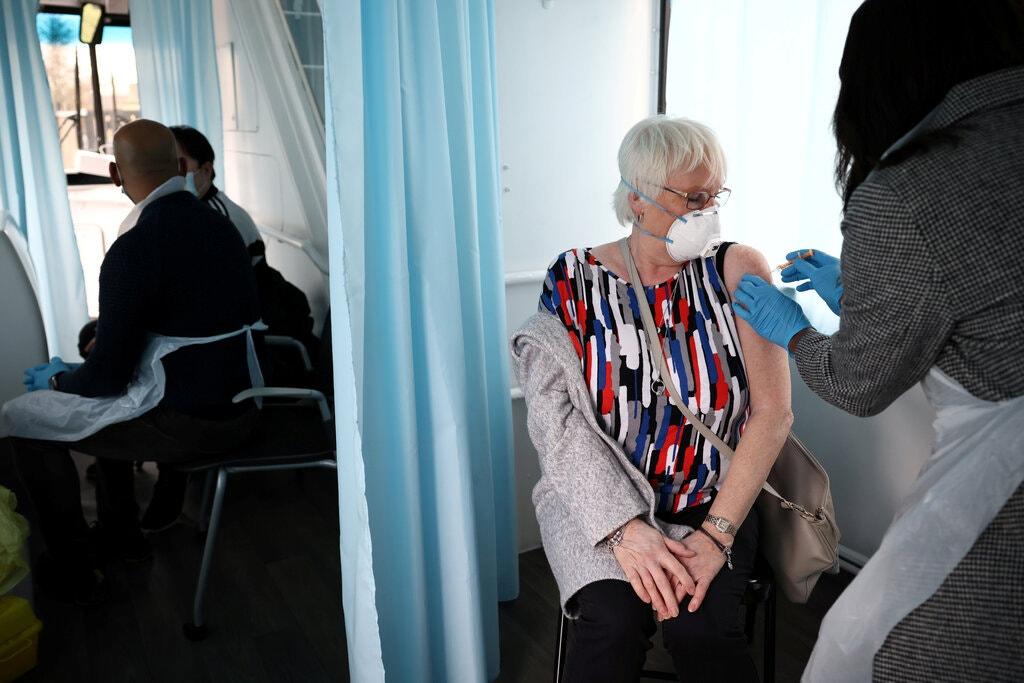 Một người phụ nữ đang tiêm vaccine AstraZeneca trong một chiếc xe buýt được dùng làm điểm tiêm chủng di động tại London. Ảnh: New York Times.