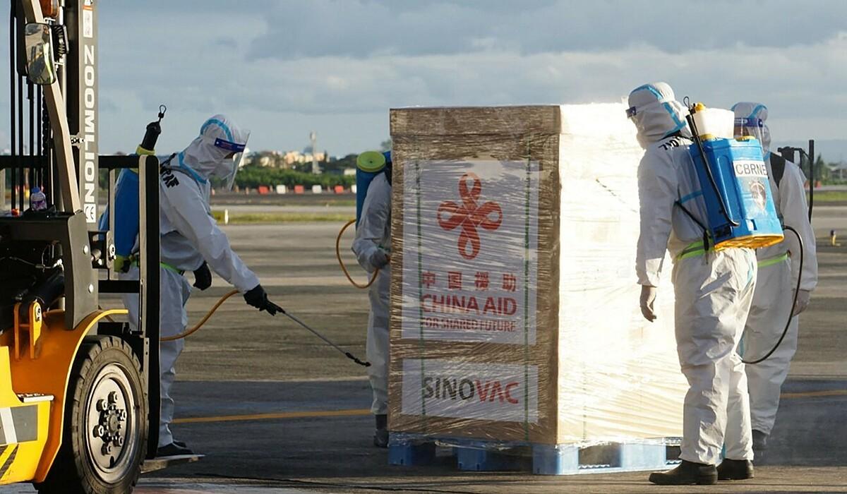 Nhân viên y tế khử trùng một thùng vaccine Sinovac sau khi được chuyển đến Manila. Ảnh: AFP