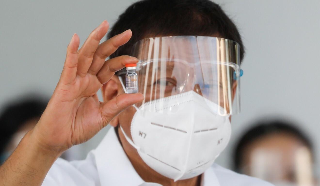 Tổng thống Rodrigo Duterte cầm một lọ vaccine Covid-19 của Sinovac. Ảnh: Reuters