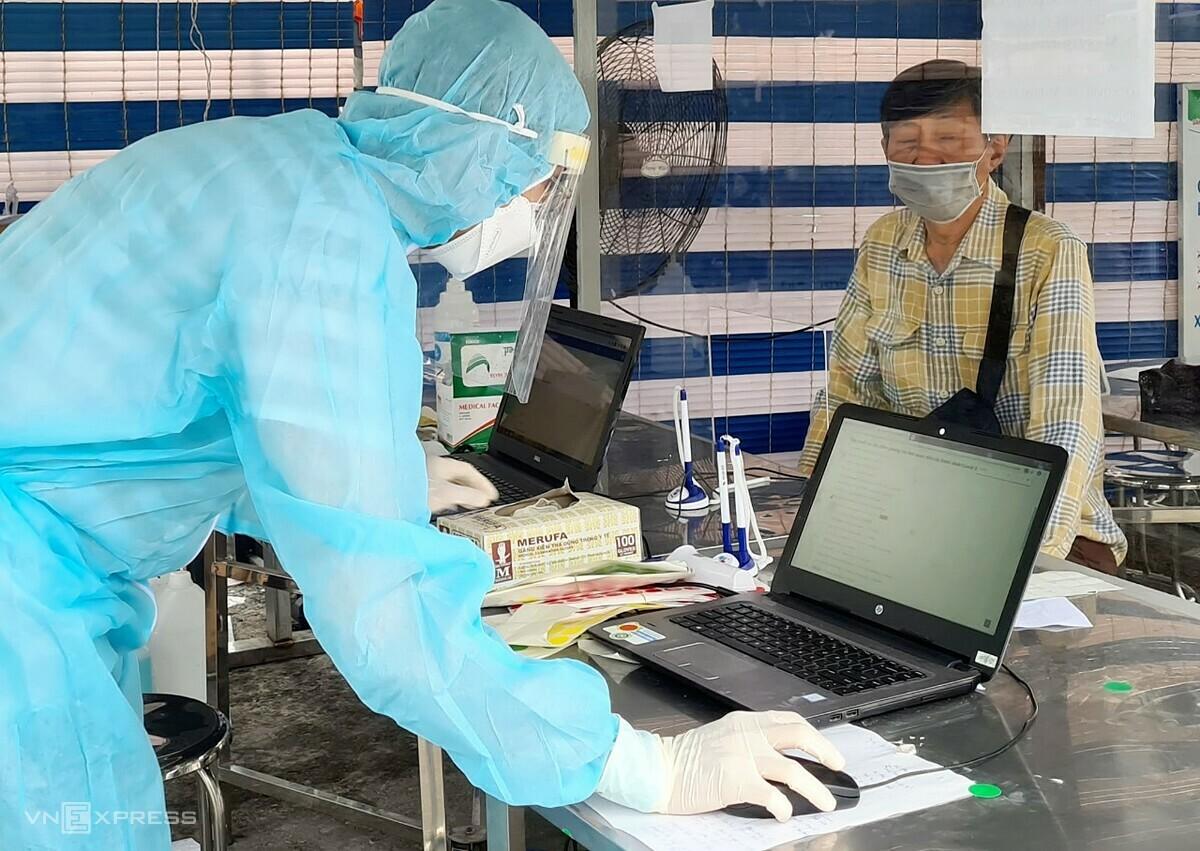 Nhân viên Bệnh viện Quân y 175 hỗ trợ người đến khám khai báo y tế điện tử. Ảnh: Lê Phương.