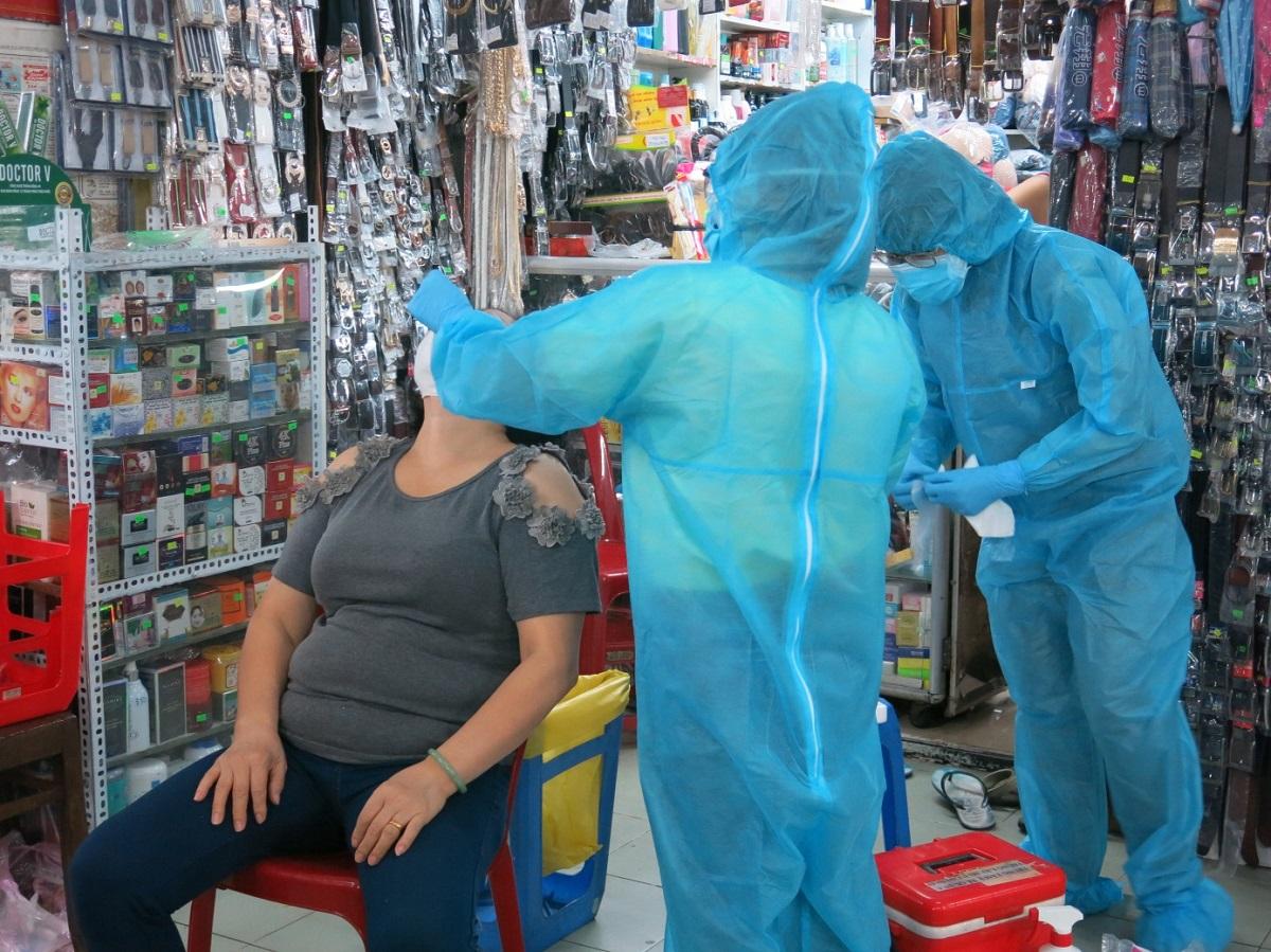 [Caption]Nhân viên y tế Quận 4, TP HCM lấy mẫu xét nghiệm Covid-19 cho tiểu thương tại chợ Xóm Chiếu. Ảnh: