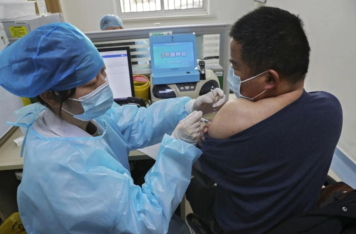 Nhân viên y tế tiêm vaccine Covid-19 cho một người đàn ông tại Trung Quốc. Ảnh: AP