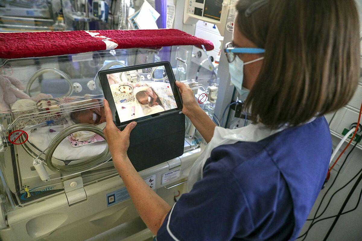 Một y tá quay video trẻ sơ sinh trong khoa sản tại Bệnh viện Frimley Park ở Surrey, Anh, năm 2020. Ảnh: Zuma Press