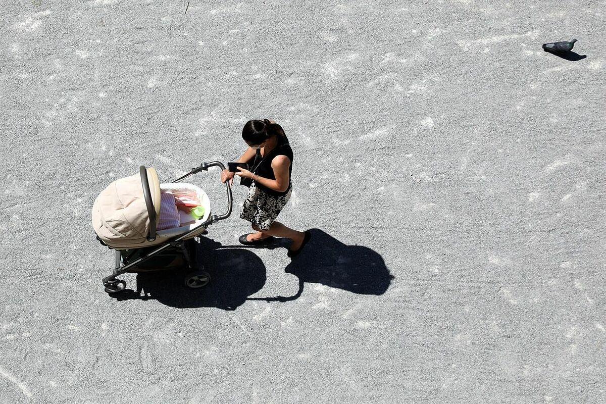 Một phụ nữ Italy đẩy xe nôi trên đường phố trong tình trạng giãn cách xã hội. Ảnh: EPA