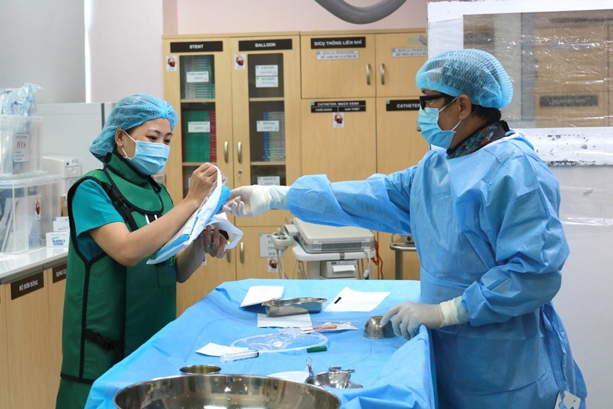 Điều dưỡng Nguyễn Thị Diệp hỗ trợ bác sĩ tại phòng can thiệp nội mạch. Ảnh: Lê Cầm
