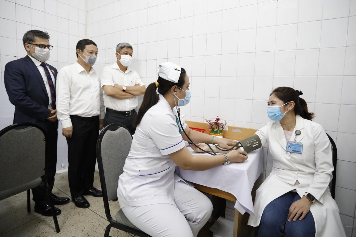 Thứ trưởng Bộ Y tế Nguyễn Trường Sơn (thứ 3 từ trái sang) theo dõi quá trình đo sinh hiệu, khám sàng lọc trước tiêm của bác sĩ Xuân (bìa phải). Ảnh: Hữu Khoa.