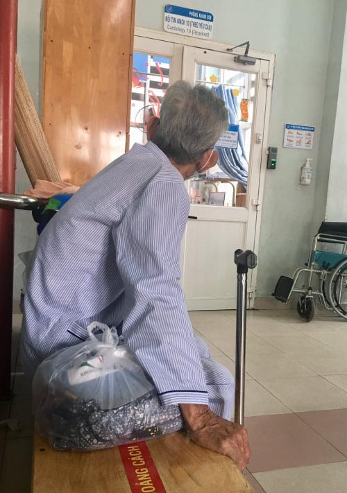 Cụ ông ngồi chờ vợ thay quần áo bệnh nhân để về nhà. Ảnh: Bệnh viện cung cấp.