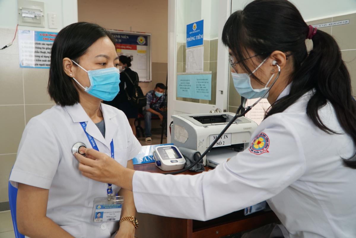 Dược sĩ Bích Hồng được đo nhịp tim và khai thác tiền sử dịch tễ trước khi tiêm vaccine Covid-19. Ảnh: Thư Anh.
