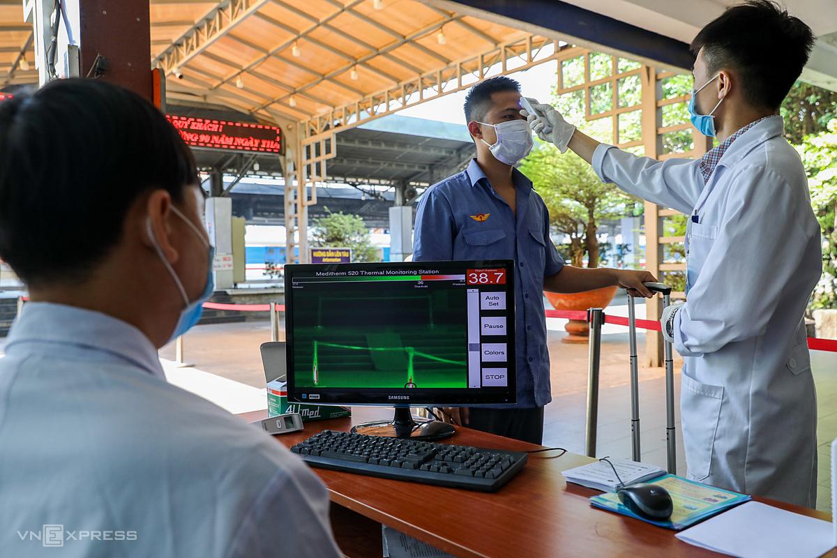 Nhân viên y tế tiến hành đo thân nhiệt cho hành khách tại ga Sài Gòn. Ảnh: Quỳnh Trần