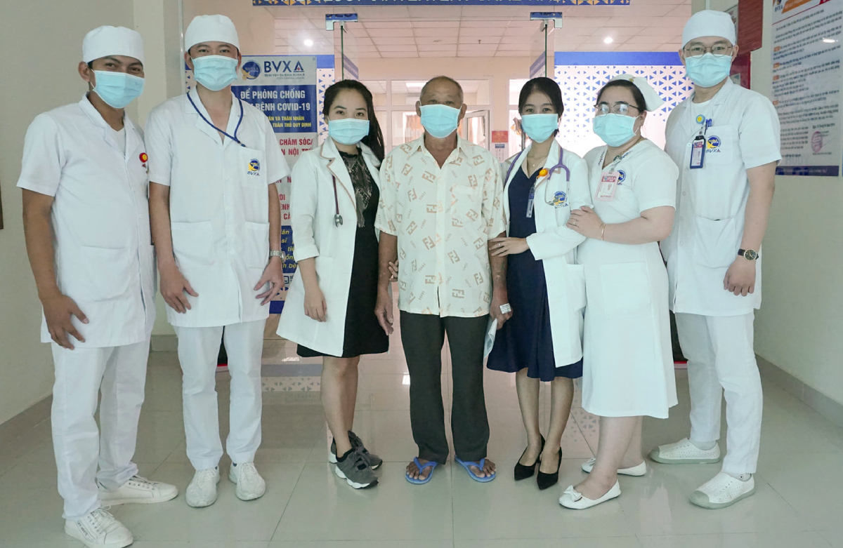 Bệnh nhân (giữa) đi lại bình thường, chụp ảnh lưu niệm cùng các bác sĩ, điều dưỡng trước khi xuất viện. Ảnh: Bệnh viện cung cấp.