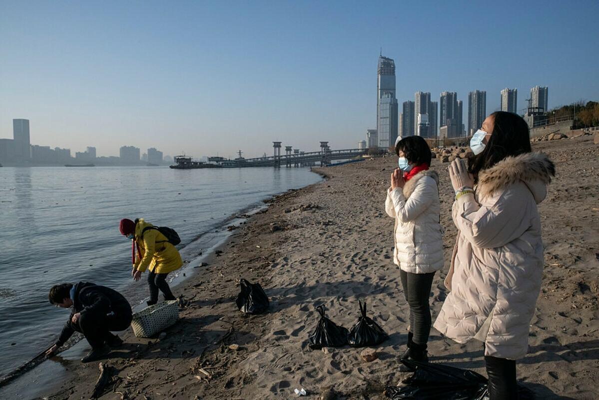 Người dân cầu nguyện dọc bờ sông Dương Tử ở Vũ Hán. Ảnh: NY Times