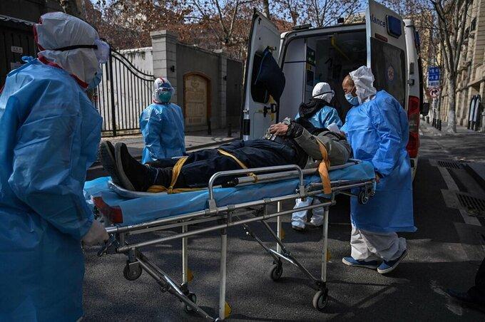 Các nhân viên y tế Vũ Hán đưa một bệnh nhân Covid-19 vào viện, tháng 1/2020. Ảnh:AFP