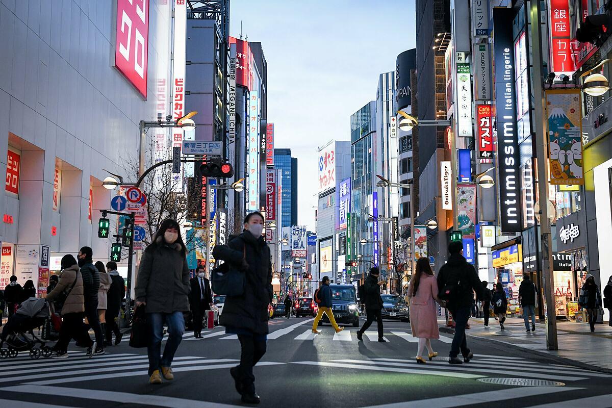 Người dân đeo khẩu trang ngừa Covid-19 trên đường phố Tokyo. Ảnh: NY Times