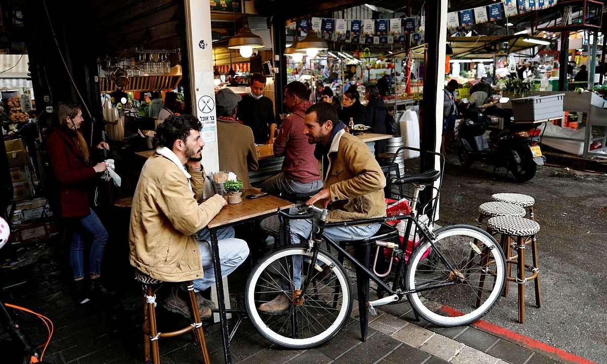 Người dân Israel trò chuyện trong một nhà hàng ở Tel Aviv hồi tháng 3. Ảnh: Reuters