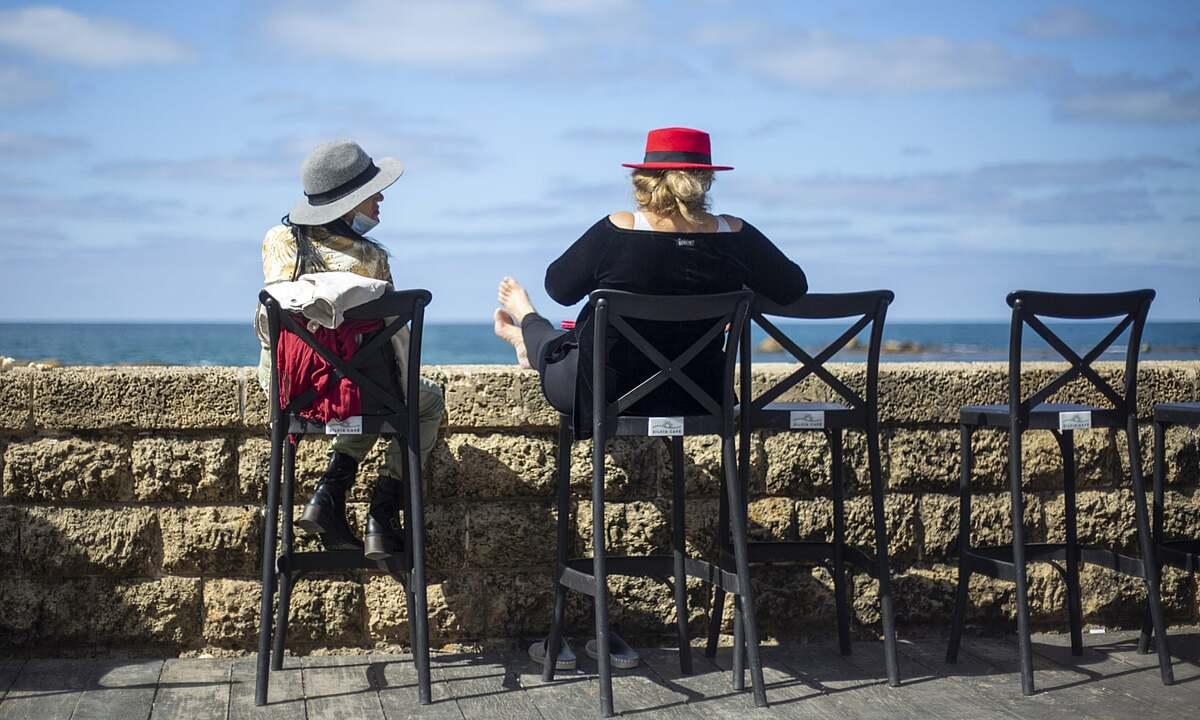 Hai người phụ nữ ngồi trong quán cà phê nhìn ra biển Địa Trung Hải ở Tel Aviv. Ảnh: AP