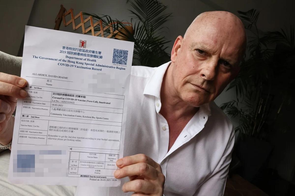 David Allardice cầm giấy chứng nhận đã tiêm liều vaccine Covid-19 đầu tiên của Sinovac do Trung tâm thể thao Vịnh Kowloon phát. Ảnh: SCMP