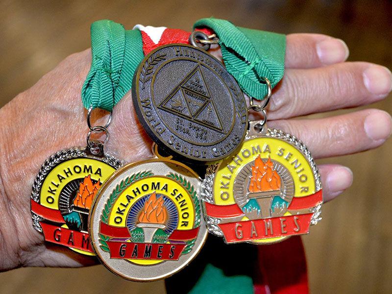 Ông Gipson khoe những tấm huy chương từ các giải đủa cấp bang và thế giới. Ảnh: Cherokee Phoenix.