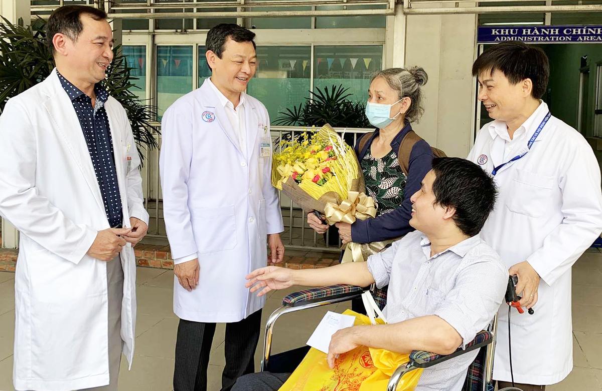 Tiến sĩ Nguyễn Tri Thức, Giám đốc Bệnh viện Chợ Rẫy (thứ hai từ trái sang) cùng các bác sĩ đến tặng hoa chúc mừng, tiễn mẹ con bệnh nhân Phan Hữu Nghiêm rời bệnh viện về nhà sau 11 năm điều trị. Ảnh: An Mỹ.