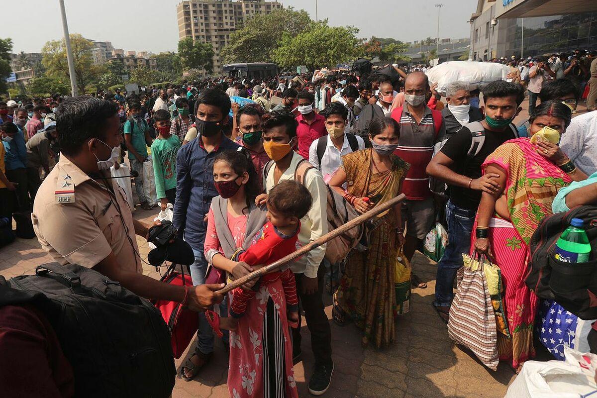 Một cảnh sát đang giữ trật tự đám đông chờ tàu ở Mumbai ngày 14/4. Ảnh: AP.