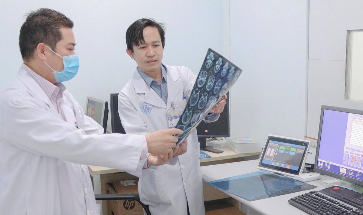 Tiến sĩ Tôn Thanh Trà (bên trái) trao đổi cùng đồng nghiệp về phim chụp CT Scan của bệnh nhân. Năm 2020, bệnh viện trang bị thêm máy CT Scan mới. Ảnh do bệnh viện cung cấp.