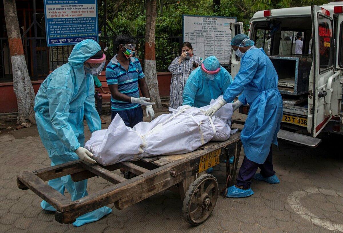 Nhân viên y tế chuyển thi thể của một phụ nữ nhiễm nCoV đến lò hoả táng ở New Delhi. Ảnh: Reuters