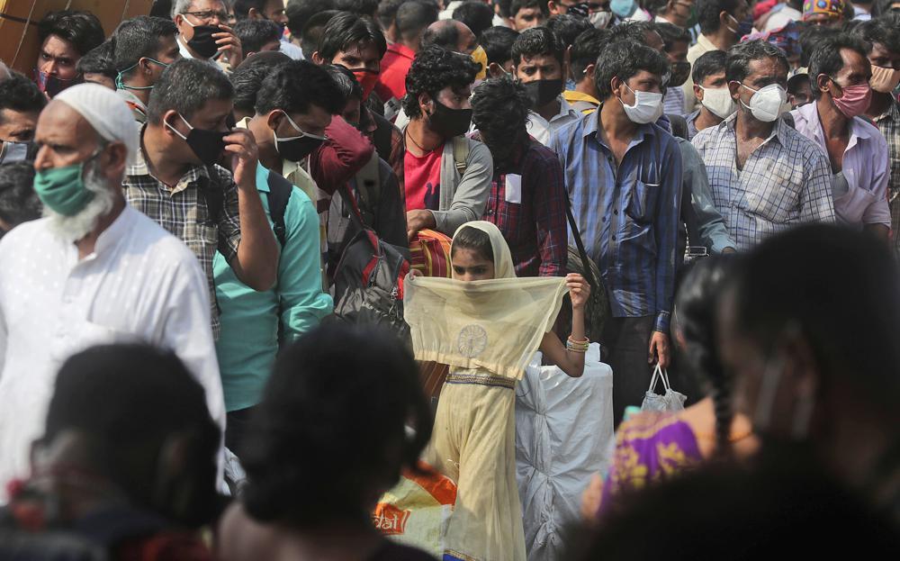 Người dân đeo khẩu trang, xếp hàng chờ tàu để rời khỏi Mumbai. Ảnh: AP.