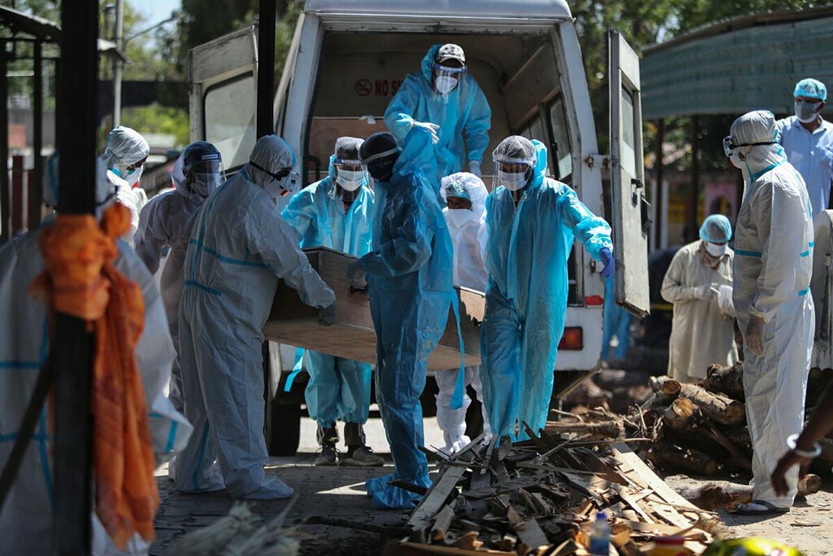 Nhân viên y tế khiêng thi thể bệnh nhân mắc Covid-19 đến lò hoả táng ở Jammu, Ấn Độ, ngày 25/4. Ảnh: AP