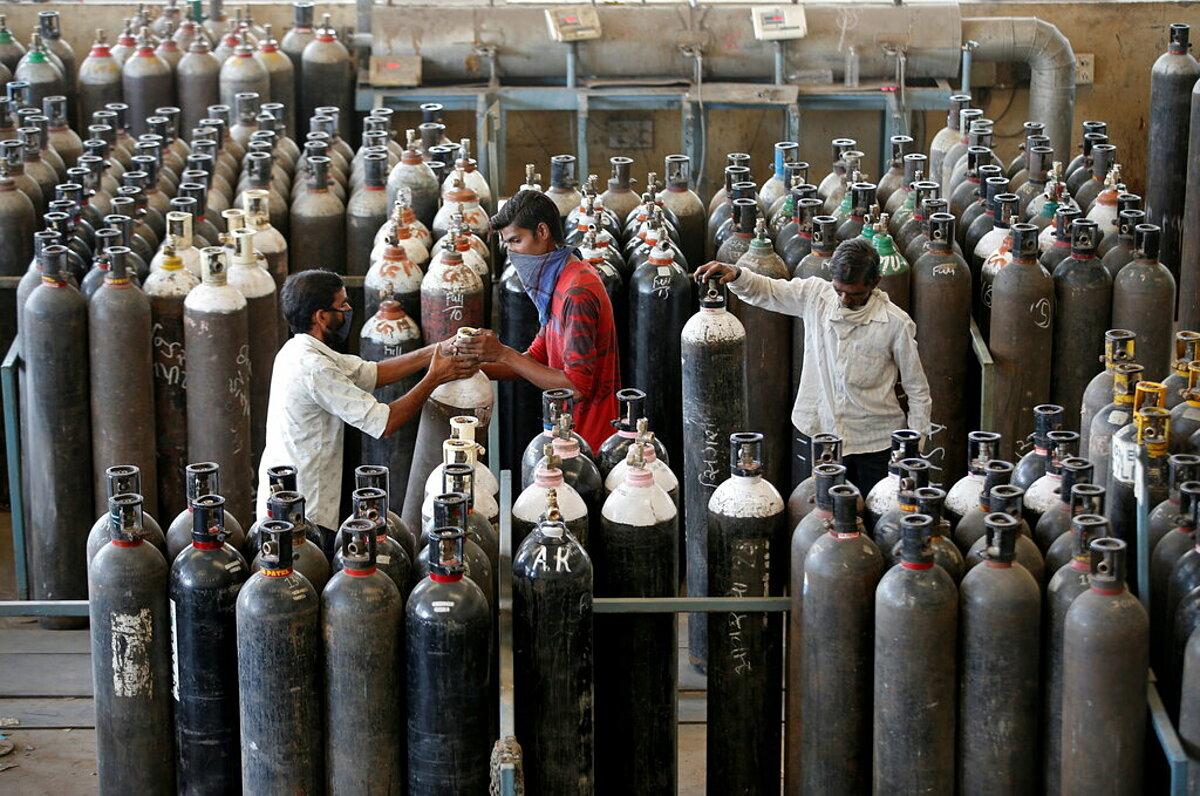 Công nhân nạp oxy y tế vào bình, chuẩn bị chuyển đến bệnh viện ở Ahmedabad, Ấn Độ, ngày 24/4. Ảnh: Reuters
