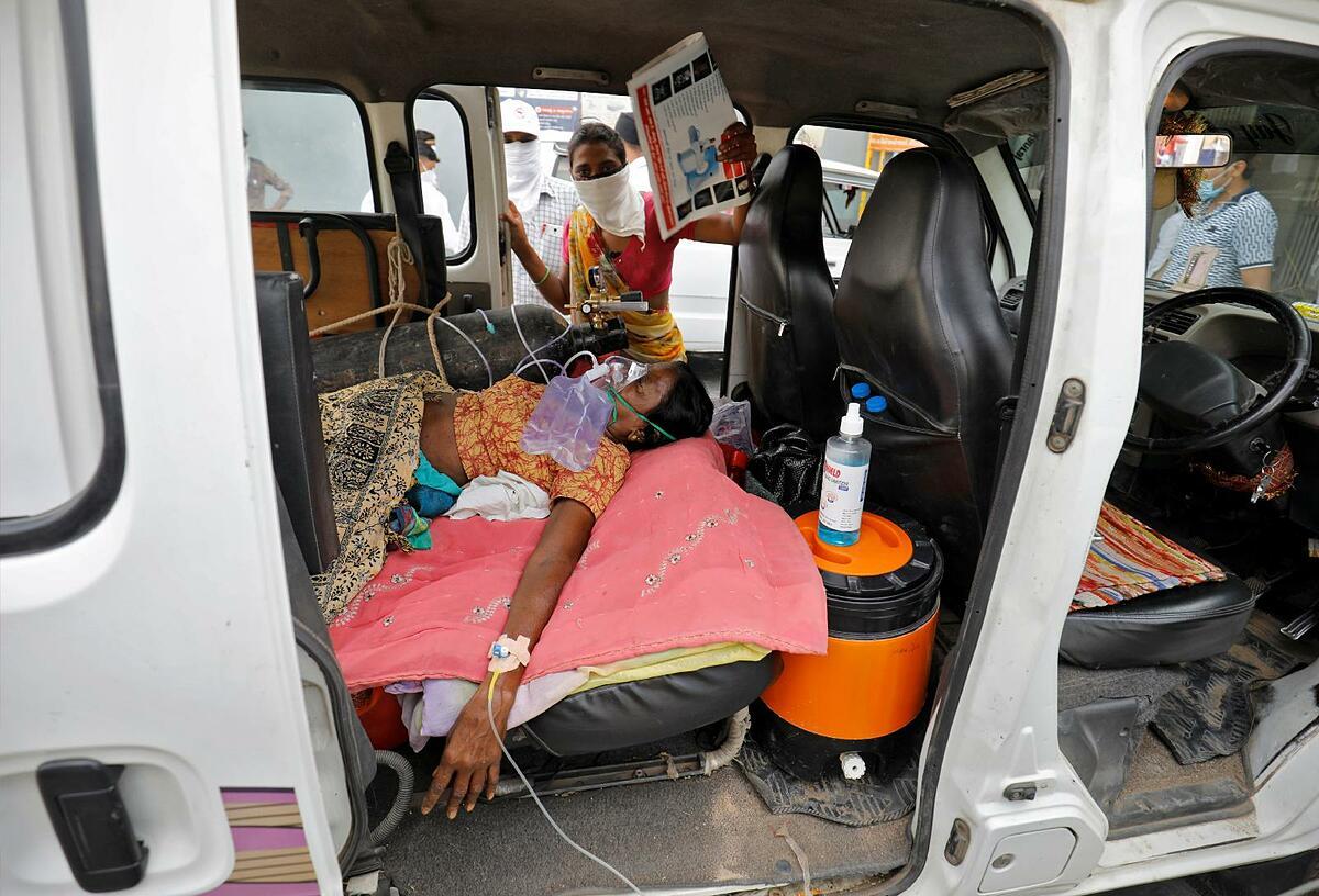 Bệnh nhân đeo mặt nạ oxy trong bãi đỗ xe của một bệnh viện ở Ahmedabad, Ấn Độ, ngày 26/4. Ảnh: CNS
