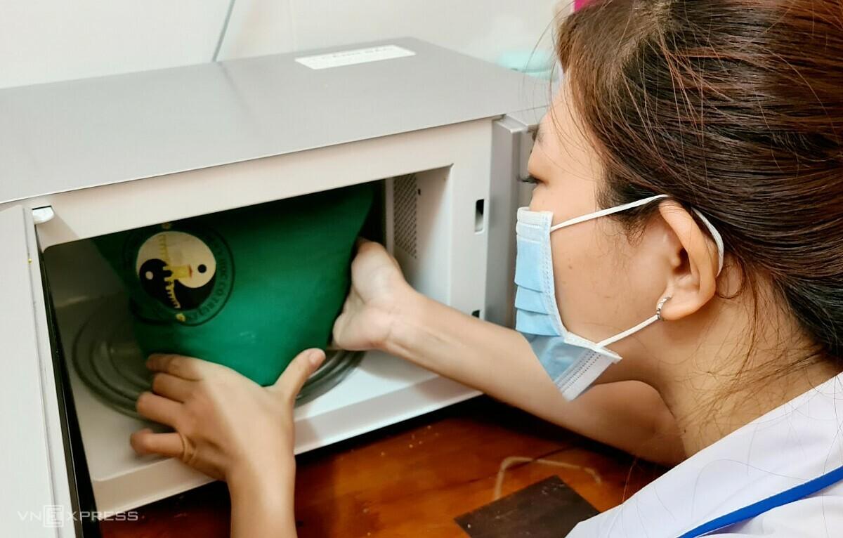 Túi chườm thảo dược được làm nóng trước khi chườm cho bệnh nhân. Ảnh: Lê Phương.