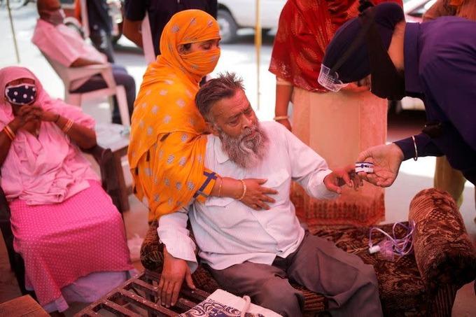 Một tình nguyện viên đo nồng độ oxy trong máu một người đàn ông trước khi hỗ trợ ông thở oxy miễn phí tại đền Sikh ở Ghaziabad, ngoại ô New Delhi, hôm 3/5. Ảnh:Reuters