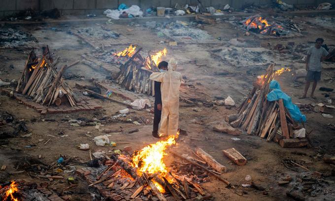Gia đình nạn nhân Covid-19 đứng ôm nhau tại khu hỏa táng ở New Delhi hôm 26/4. Ảnh: AFP.