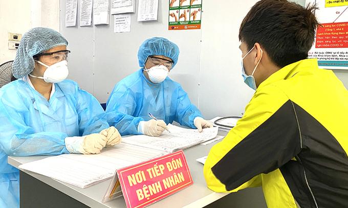 Bác sĩ bệnh viện Hà Đông đang sàng lọc người có biểu hiện ho, sốt tại phòng khám sàng lọc bệnh nhân nghi Covid-19. Ảnh:Thùy An