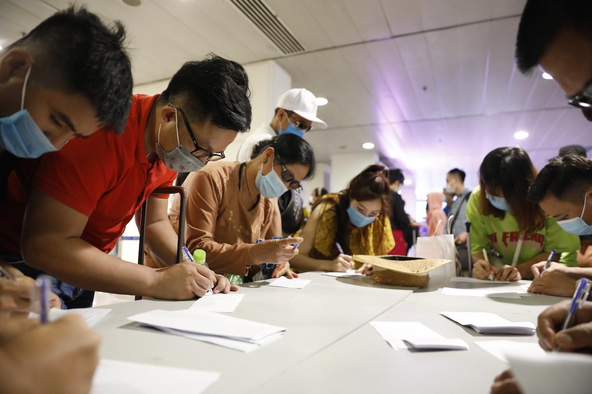 Hành khách khai báo y tế để chuẩn bị lấy mẫu xét nghiệm sau khi đến sân bay Tân Sơn Nhất, TP HCM ngày 6/5. Ảnh: Hữu Khoa