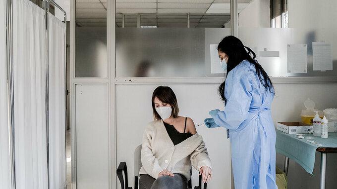 Một phụ nữ Anh được tiêm vaccine AstraZeneca tại London, tháng 2/2021. Ảnh: NY Times
