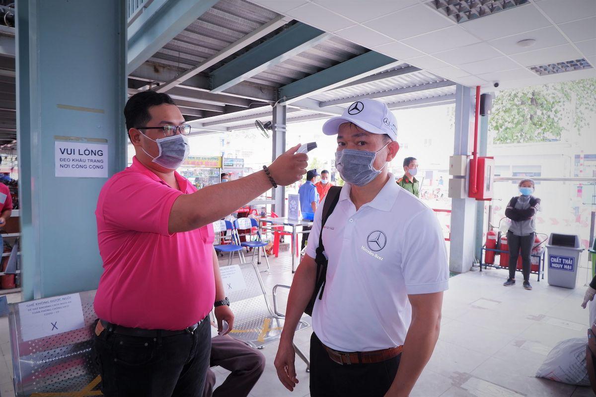 Nhân viên đo thân nhiệt cho hành khách tại bến xe An Sương, TP HCM chiều 6/5/2021. Ảnh: Phú Khánh HCDC