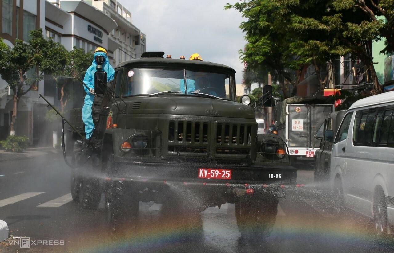 Bộ đội phun thuốc khửa khuẩn ở đường Đống Đa trước quán bar Phương Đông ở Đà Nẵng. Ảnh: Đắc Thành.