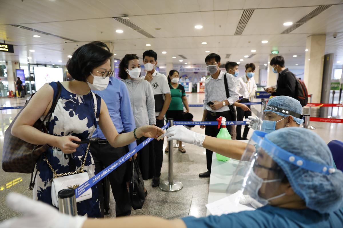 Hành khách xếp hàng chờ lấy mẫu xét nghiệm nCoV tại sân bay Tân Sơn Nhất sáng 6/5. Ảnh: Hữu Khoa.
