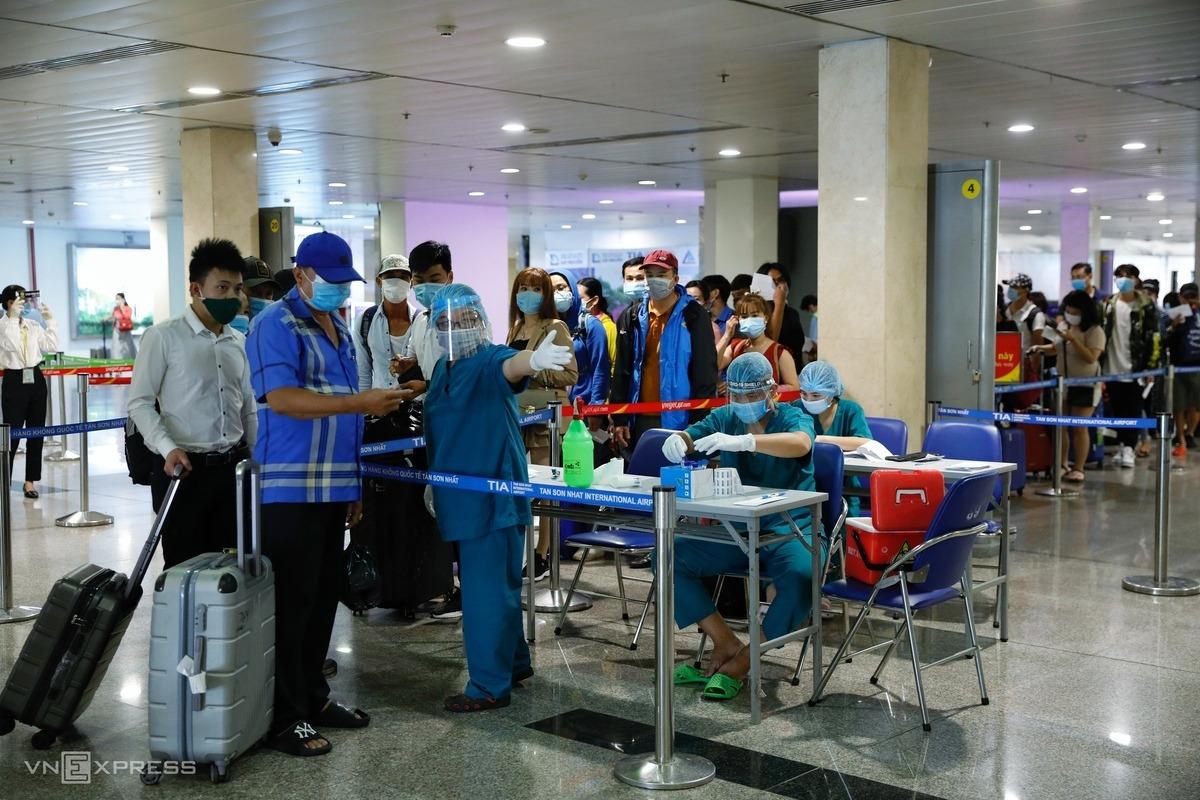 Hành khách được nhân viên y tế hướng dẫn vào khu vực chờ lấy mẫu tại sân bay Tân Sơn Nhất, ngày 6/5. Ảnh: Hữu Khoa.