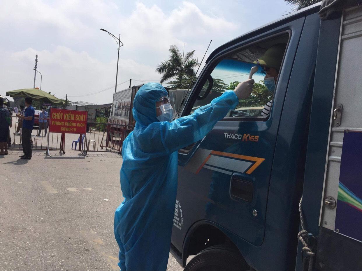 Nhân viên y tế đo thân nhiệt tại chốt Cầu Hồ, Bắc Ninh sáng 12/5. Ảnh: Ngọc Ly