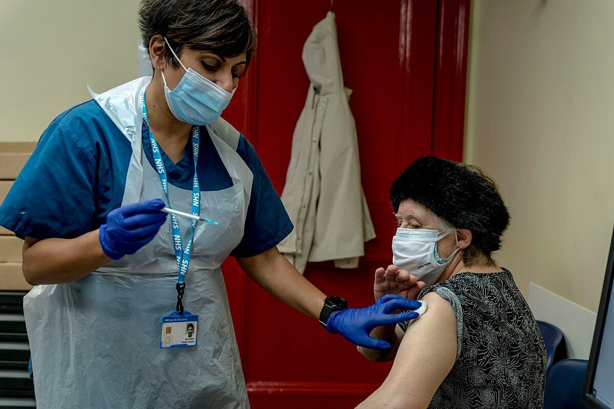 Một cụ bà 74 tuổi được tiêm vaccine Covid-19 của Pfizer tại Trung tâm Bloomsbury Surgery ở London, tháng 1/2021. Ảnh: NY Times