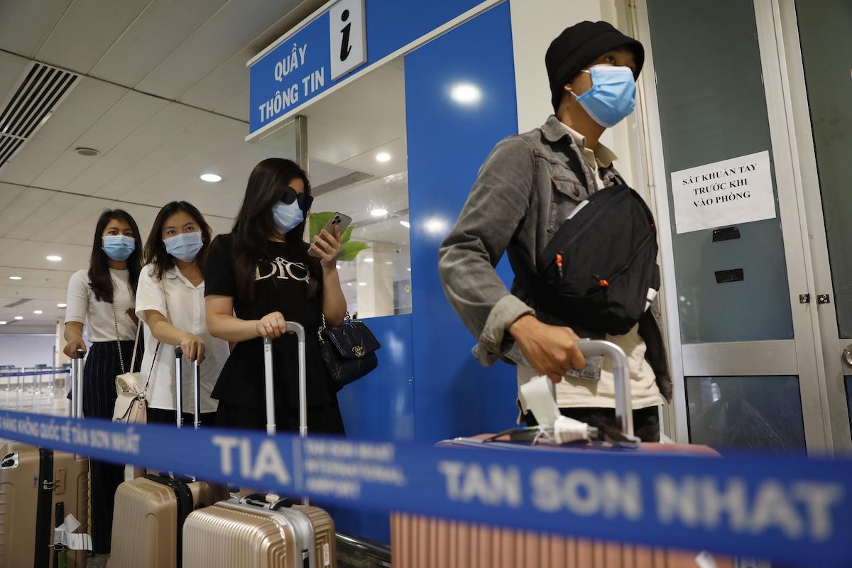 Hành khách khai báo y tế và chuẩn bị lấy mẫu xét nghiệm sau khi xuống máy bay tại sân bay Tân Sơn Nhất. Ảnh: Hữu Khoa