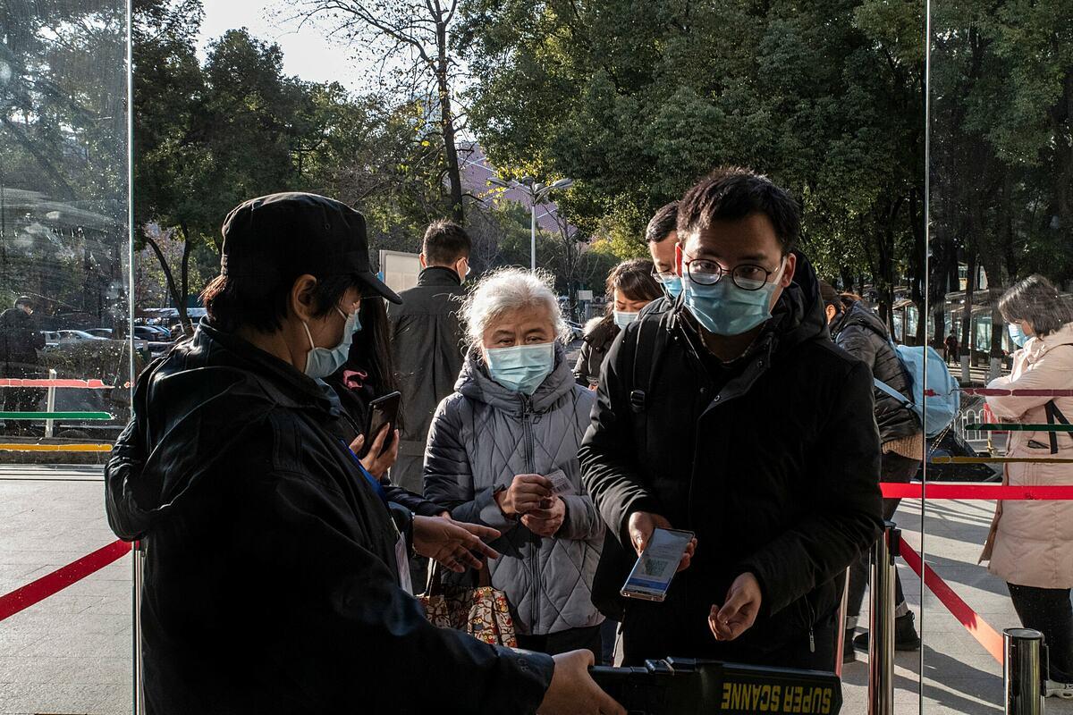 Nhân viên bệnh viện Zhongnan ở Vũ Hán quét mã QR sức khoẻ cho người dân tại lối ra vào. Ảnh: NY Times
