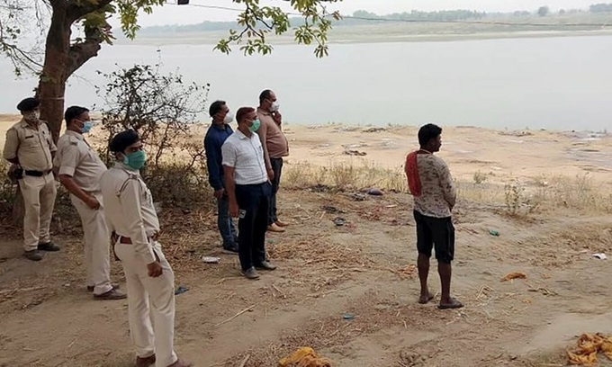 Cảnh sát giám sát việc chôn cất các thi thể trôi dạt vào bờ sông Hằng ở làng Chausa, huyện Buxar, bang Bihar, hôm 11/5. Ảnh: PTI.