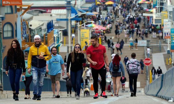 Người đi bộ không đeo khẩu trang ở bến tàu ở Santa Monica, bang California hôm 13/5. Ảnh: AP.