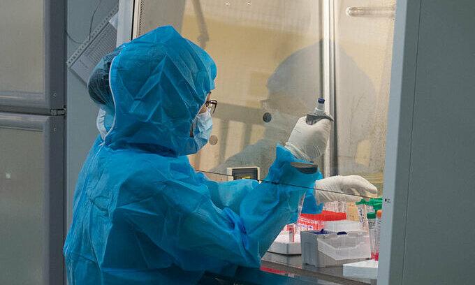 Nhân viên xét nghiệm tách vật liệu di truyền của virus từ mẫu bệnh phẩm trong tủ an toàn sinh học tại Bệnh viện Bệnh nhiệt đới Trung ương. Ảnh:Chi Lê.