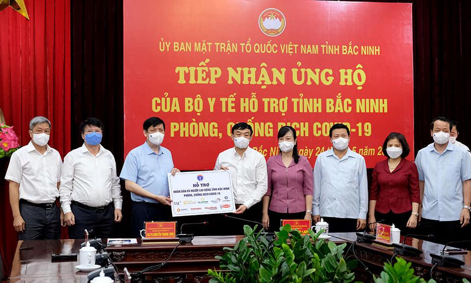 Bộ trưởng Long (áo xanh) trao quà hỗ trợ tỉnh Bắc Ninh sáng 24/5. Ảnh: MOH.