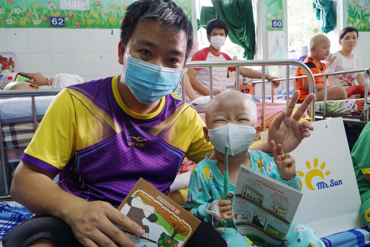 Một cô bé bốn tuổi mắc bệnh ung thư máu cười tít mắt khi nhận được cuốn sách yêu thích từ dự án Mặt trời Hy vọng. Ảnh: Thư Anh.