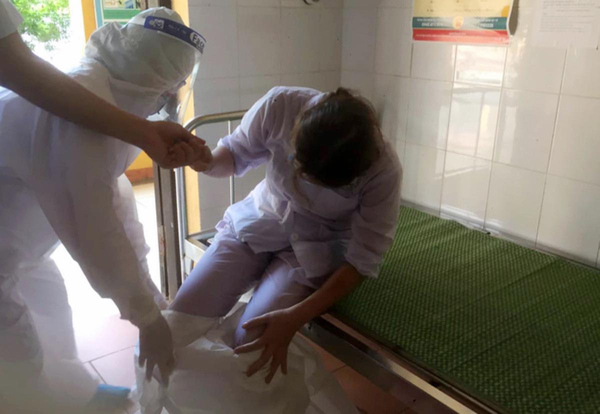 Y sĩ Lê Thị Nhung, Trung tâm y tế huyện Thuận Thành, Bắc Ninh ướt sũng người và kiệt sức không thể cởi được bộ đồ bảo hộ, sau đó nôn và ngất đi hôm làm việc 9/5 khi đi chi viện cho ổ dịch Mão Điền. Ảnh: Nguyễn Hướng.